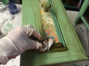 This shows the process of rubbing on the antiquing glaze.